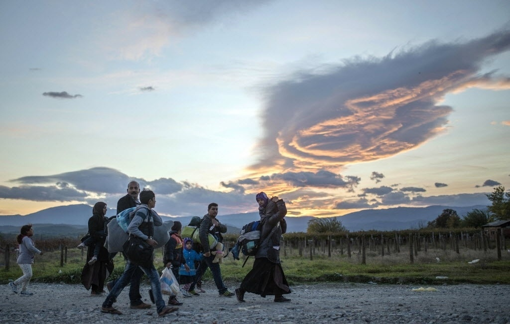 10.nov.2015 - Refugiados caminham para pegar um ônibus para a Sérvia após sair de centro de registro na cidade de Gevgelija, na Macedônia. Sete organizações humanitárias lançaram um apelo à comunidade internacional para adotar um plano ambicioso para promover o trabalho de refugiados sírios nos países de acolhimento. O plano propõe