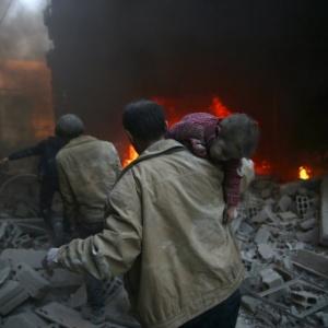 Homem carrega criança ferida em ataque à bomba de forças leais ao presidente sírio, Bashar al-Assad, na cidade de Douma, no leste de Ghouta (Síria)