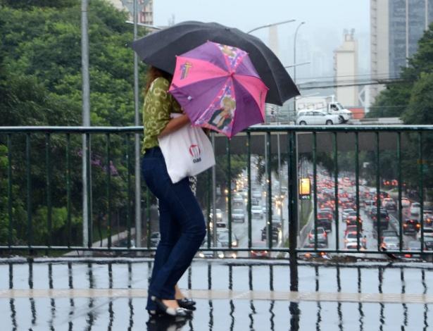 10.mar.2016 - Pedestre se protege da chuva no viaduto Santa Generosa, no Paraíso, em São Paulo. A chuva desta quinta-feira (10) fez a capital paulista bater o recorde de trânsito do ano pela manhã e deixou toda a cidade em estado de atenção para alagamentos