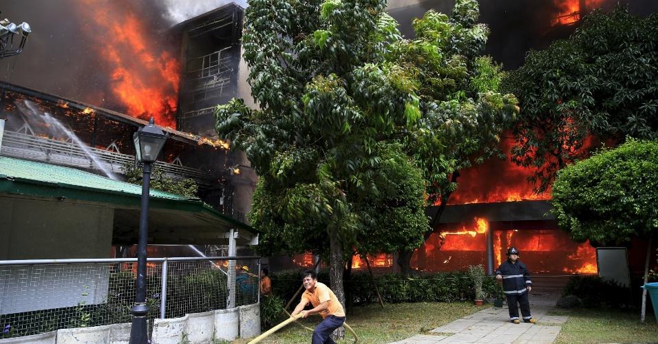 2.abr.2016 - Filipino ajuda bombeiro que tenta apagar incêndio na Academia de Artes e Ciências da Universidade do Oriente, em Manila. As autoridades investigam a causa do fogo que consome grande parte do edifício, segundo a imprensa local