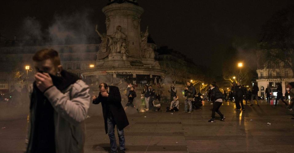 """23.abr.2016 - Manifestantes cobrem o rosto com lenços para se proteger do gás lacrimogêneo lançado por policiais sobre ato Nuit Debout (Noite Acordada) realizado na praça de la Republique, em Paris. Os Nuit Debout, cada vez mais recorrentes na França, vêm sendo reprimidos pela polícia, que acusa a presença de """"desordeiros"""" entre os manifestantes. Os protestos começaram contra propostas do governo de reformas trabalhistas, porém as pautas se tornaram mais amplas e tidas como revolucionárias"""