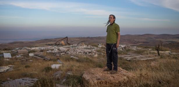 Hanamel Dorfman, 21, ao lado dos destroços de uma casa que foi demolida por autoridades israelenses no assentamento judaico de Yishuv Hadaat, na Cisjordânia