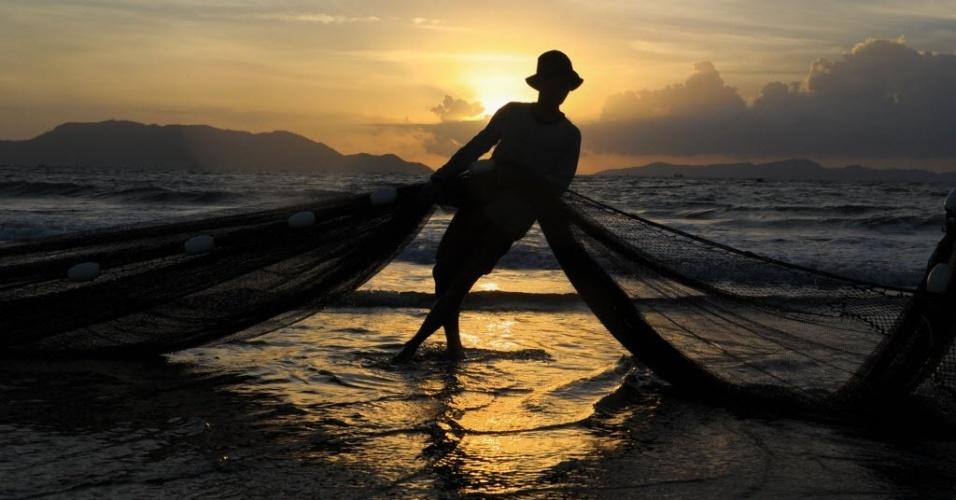 27.set.2016 - Pescador limpa rede de pesca em Banda Aceh, na Indonésia