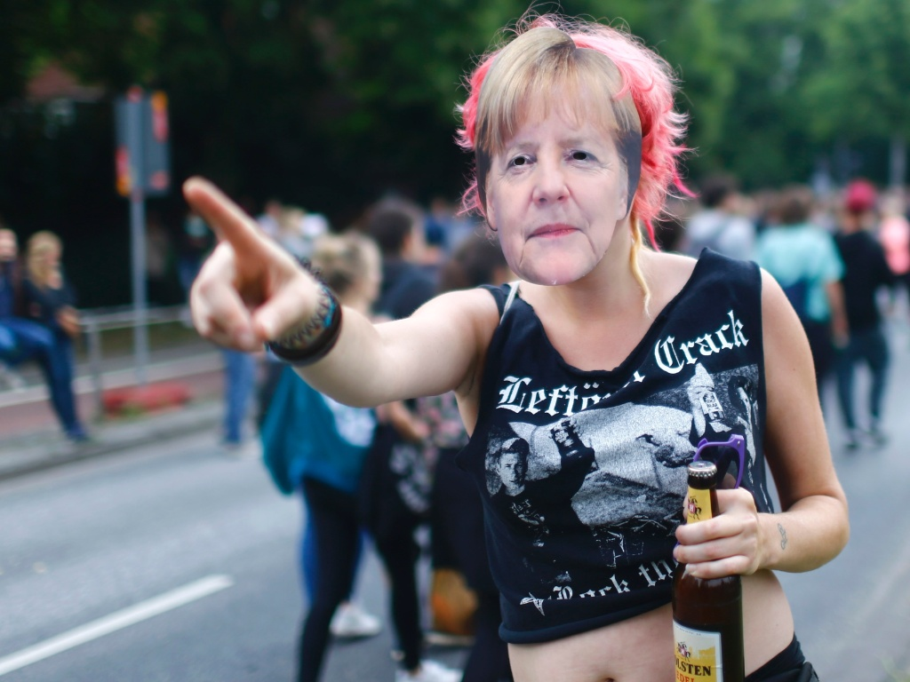 5.jul.2017 - Mulher veste máscara da chanceler Angela Merkel durante protesto contra o G20 em Hamburgo, na Alemanha