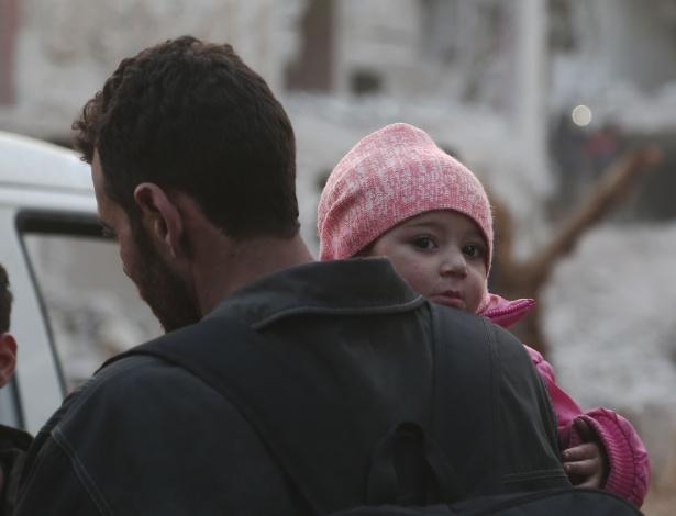 Criança síria e seu pai na noite de ontem, se preparando para deixar Ghouta Oriental - Abdulmonam Eassa/AFP Photo