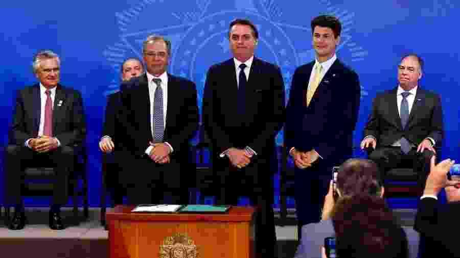 Gustavo Montezano (em pé, à dir.) toma posse como novo presidente do BNDES, ao lado do presidente Jair Bolsonaro (centro) e do ministro da Economia, Paulo Guedes (em pé, à esq.) - Divulgação/BNDES