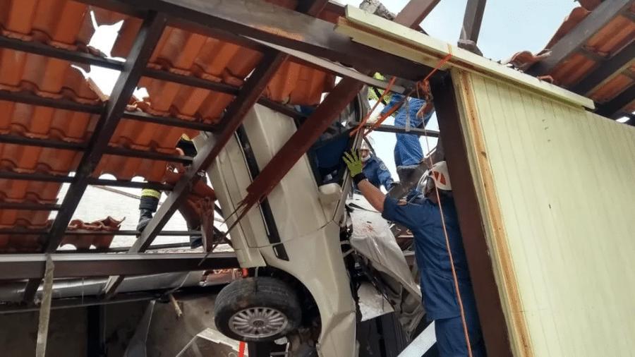 Carro ficou pendurado em um telhado depois que o motorista perdeu o controle do veículo, em Blumenau - Corpo de Bombeiros de Santa Catarina/Tenente Iakusch/Reprodução