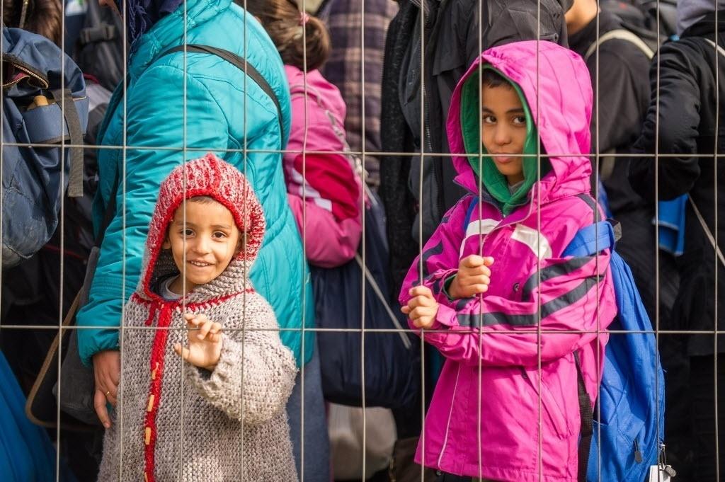25.out.2015 - Migrantes e refugiados esperam para cruzar a fronteira da Eslovênia para a Áustria neste domingo (25). A Eslovênia pediu à União Europeia forças policiais para ajudar a regular o fluxo de imigrantes