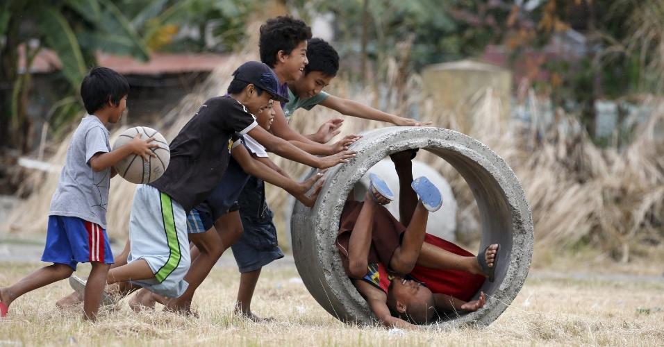 28.fev.2016 - Garotos brincam com um tubo de drenagem usado para controlar as inundações em Las Pinas, Manila (Filipinas)
