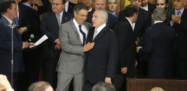 12.mai.2016 - O presidente Michel Temer (PMDB) abraça o senador Aécio Neves (PSDB-MG) durante cerimônia de posse dos novos ministros