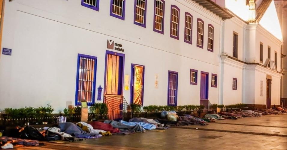 14.jun.2016 - Moradores de rua dormem em calçada no Pateo do Colégio, na zona central de São Paulo. Quem encontrar uma pessoa precisando de ajuda pode ligar para a Central de Atendimento Permanente e de Emergência da Prefeitura, que funciona 24 horas por dia. O telefone é 156. Equipes da Secretaria de Assistência e Desenvolvimento Social vão convidar essas pessoas a irem para abrigos. A população também pode ajudar doando roupas, sapatos, agasalhos e cobertores. Há diversos pontos de coleta espalhados pela cidade. No site da Campanha do Agasalho do governo estadual é possível descobrir o local mais próximo digitando o CEP da residência