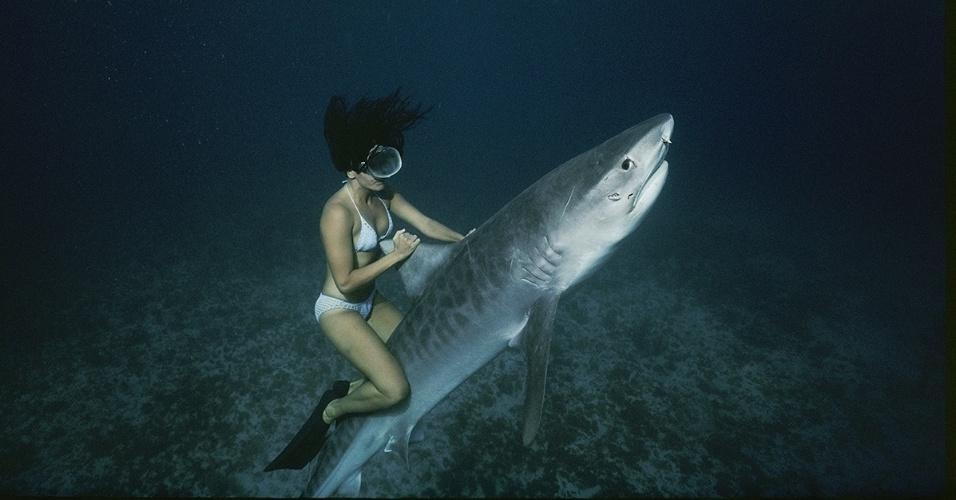 29.ago.2016  - Uma mergulhadora sobe em uma réplica de tubarão na Ilha das Mulheres, no México. A imagem foi registrada durante as gravações do filme