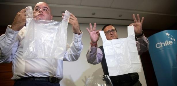 Os engenheiros chilenos Roberto Astete e Cristian Olivares mostram duas sacolas, uma de plástico e outra de material biodegradável inventada por eles
