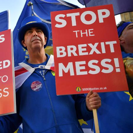 """Manifestante pró-UE em frente o parlamento de Londres. Em seus cartazes, os dizeres """"parem a bagunça do Brexit"""" e """"As coisa mudaram. É hora de reavalia-las"""" - Ben Stansall/AFP"""