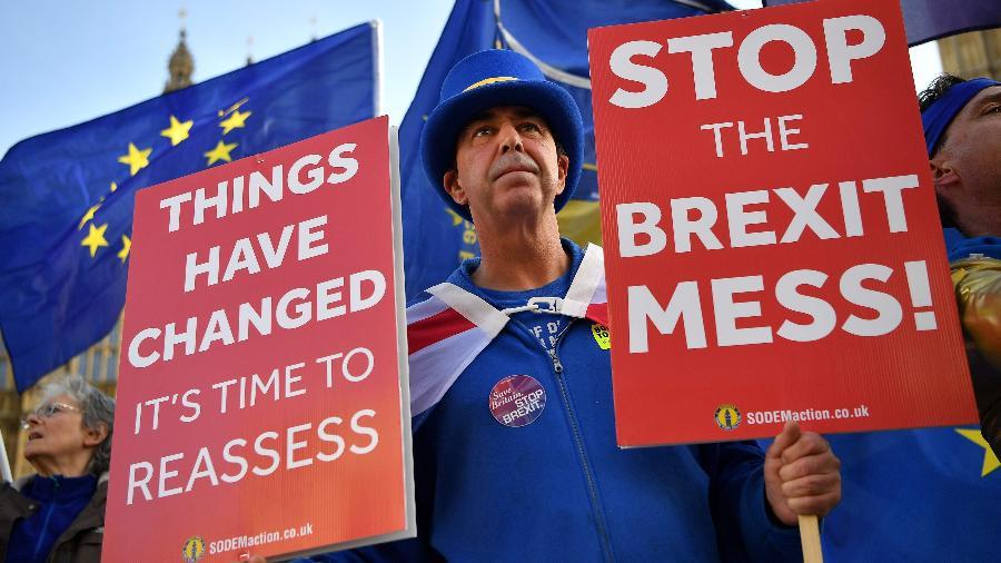 """O manifestante pró-UE, Steve Bray em frente o parlamento de Londres. Em seus cartazes, os dizeres """"parem a bagunça do Brexit"""" e """"As coisa mudaram. É hora de reavalia-las"""" - Ben Stansall/AFP"""