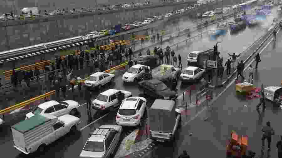 Pessoas param seus carros em uma rodovia em protesto contra aumento da gasolina em Teerã - Nazanin Tabatabaee/WANA