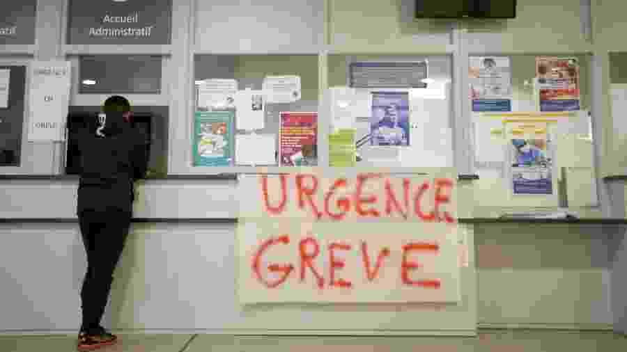 """11.dez.2019 - Paciente espera na área de atendimento de emergência no hospital Timone, em Marselha, na França. Uma faixa indicando """"emergência em greve"""" foi colocada no local por médicos residentes para denunciar a falta de recursos e más condições de trabalho - Jean-Paul Pelissier/Reuters"""