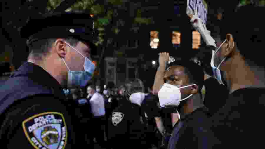 Um manifestante encara um policial durante um protesto após a morte do afro-americano George Floyd - Caitlin Ochs/Reuters