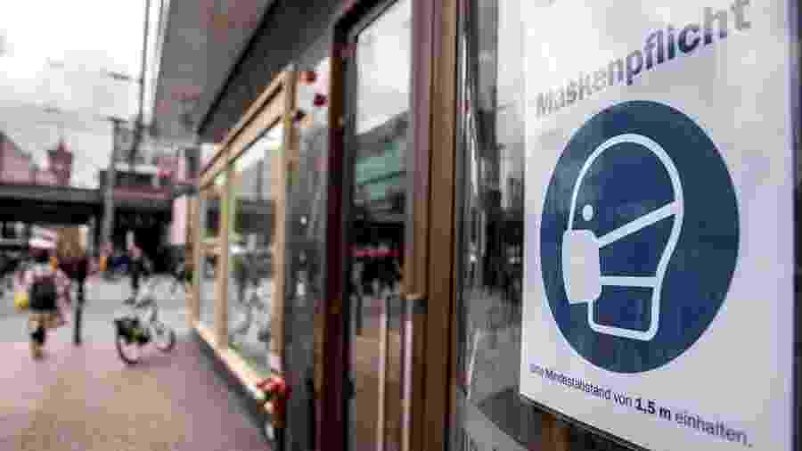 17.out.2020 - Placa sobre uso obrigatório de máscara é vista em vitrine de loja em Berlim - EFE/EPA/OMER MESSINGER