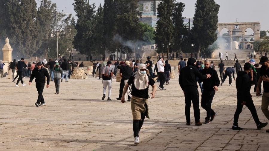 Palestinos correm após ação de forças de segurança de Israel - AHMAD GHARABLI/AFP