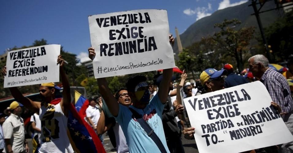 """12.mar.2016 - Manifestantes carregam cartazes com frases como """"A Venezuela exige renúncia"""" e """"A Venezuela exige referendo"""" em marcha de opositores do presidente Nicolás Maduro, neste sábado (12). Maduro enfrenta críticas da oposição em um momento de crise para o país, com grave recessão e inflação de três dígitos"""