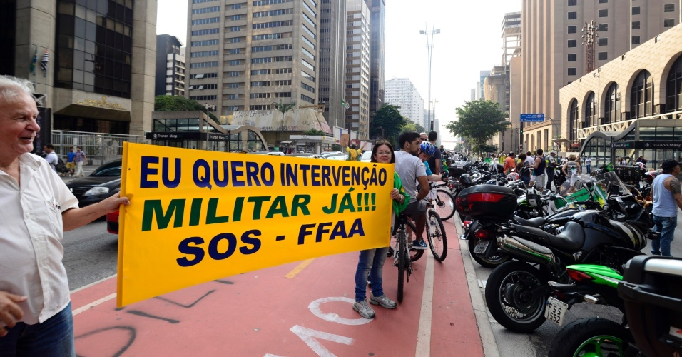 """16.abr.2016 - Motociclistas que participam de carreata a favor do impeachment da presidente Dilma Rousseff, na avenida Paulista, zona oeste de São Paulo, estendem faixa pedindo """"intervenção militar já"""""""