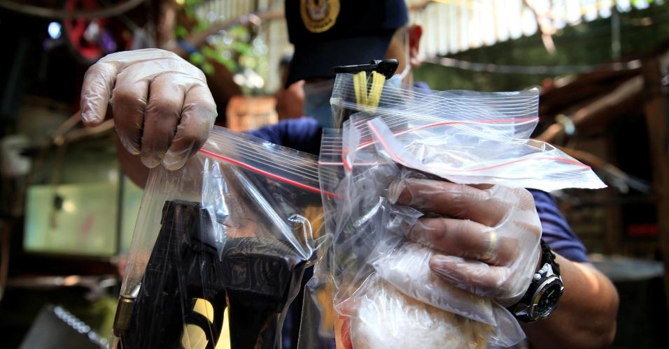 3.jul.2016 - Policial filipino exibe armas e pacotes de metaanfetamina apreendidos em operação realizada na cidade de Quiapo, na região metropolitana da capital Manila