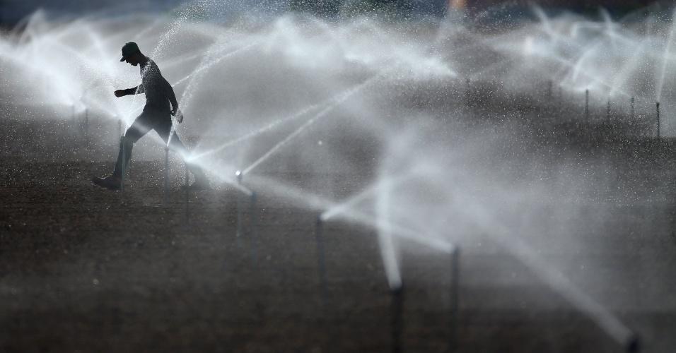 7.nov.2016 - Trabalhador caminha através da água após a criação de um sistema de irrigação em um campo agrícola, perto de Calexico, na Califórnia (EUA)