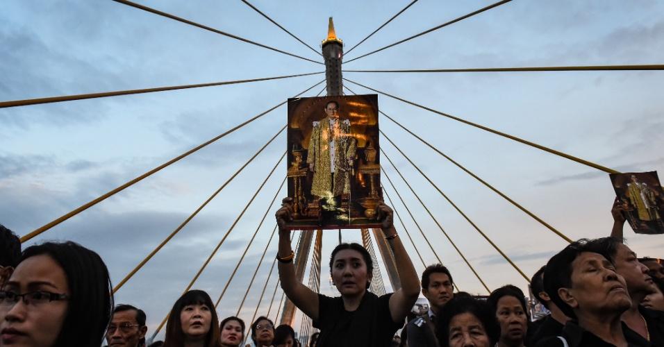 7.dez.2016 - Mulher segura no alto a imagem do rei tailandês atrasado Bhumibol Adulyadej em comemoração de seu aniversário, sobre a ponte de Bhumibol em Banguecoque (Tailândia)