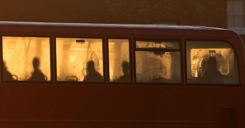 29.dez.2016 - Silhuetas de passageiros vistas pela janela de ônibus durante o nascer do sol em Londres