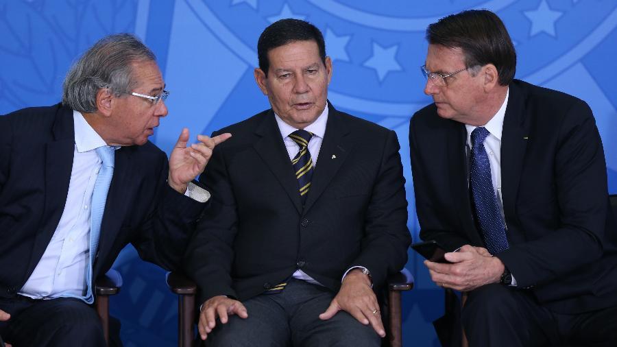 O Presidente Jair Bolsonaro conversa com o Vice Presidente General Hamilton Mourão e o ministro da Economia Paulo Guedes durante solenidade de Lançamento de Linha de Crédito do BNDES para Organizações Filantrópicas, no Palácio do Planalto - Andre Coelho/Folhapress