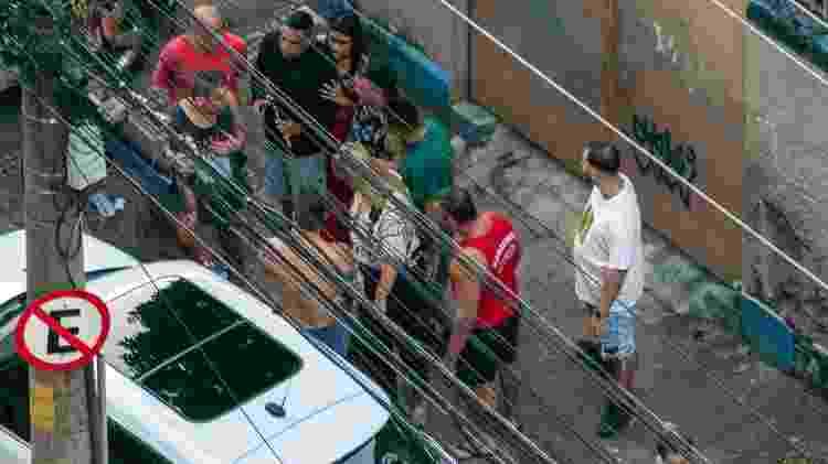 30.mai.2020 - Ainda próximo de Ticyana, no chão (não é possível vê-la na imagem), Luiz Eduardo segura o martelo usado por ela para quebrar o retrovisor e o vidro traseiro do seu carro. Aparentando estar mais calma, a mulher que a agrediu o abraça, por trás - Reprodução - Reprodução