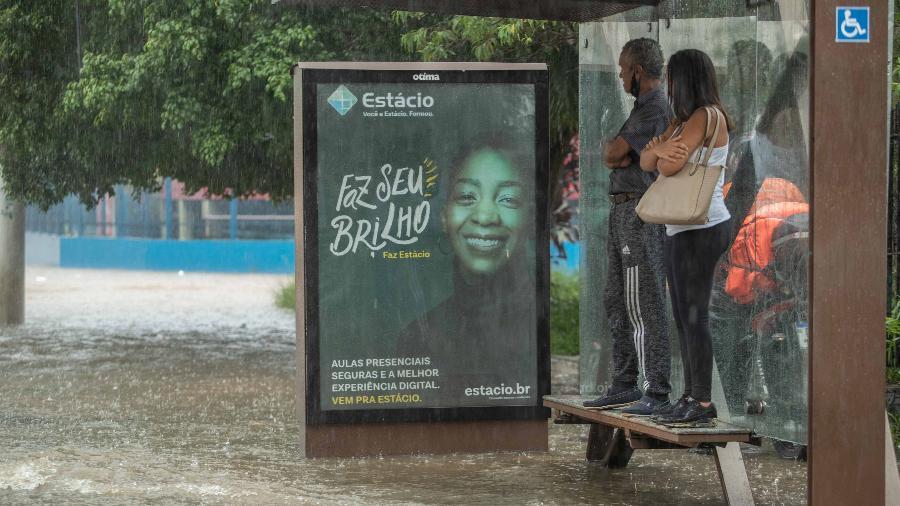 Pessoas se abrigam sob ponto de ônibus em meio a alagamento na Av. Interlagos, na zona sul de São Paulo - Daniel Teixeira/Estadão Conteúdo
