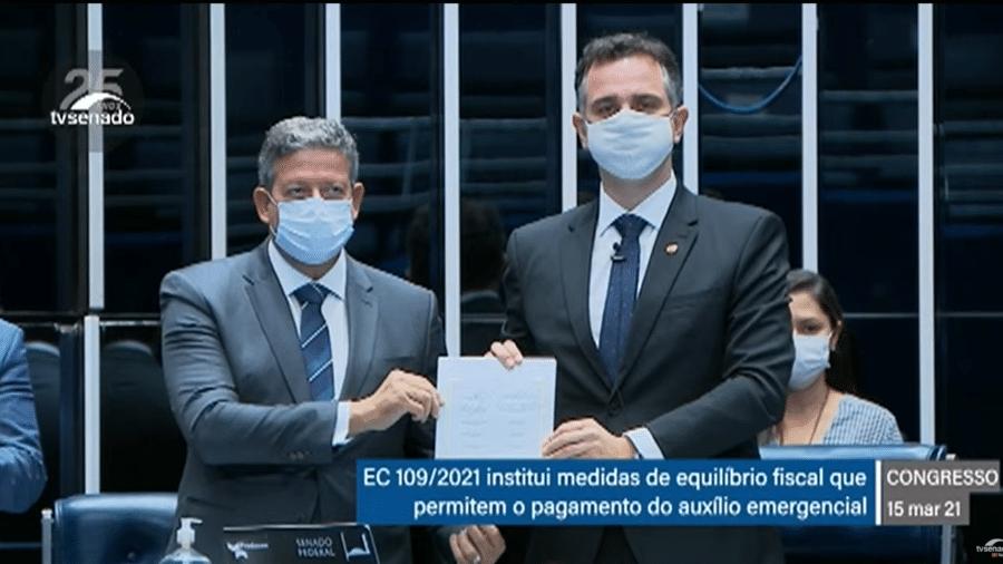 O presidente da Câmara, Arthur Lira (PP-AL), e o presidente do Senado, Rodrigo Pacheco (DEM-MG), durante sessão solene que promulgou a PEC que recria o auxílio - Reprodução/TV Senado