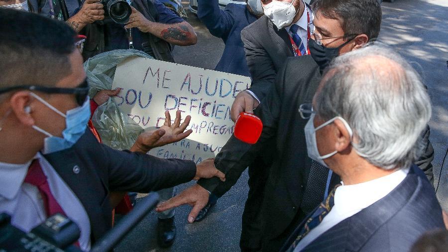Ministro da Economia Paulo Guedes é abordado por um pedinte ao retornar ao ministério após um evento com o presidente Jair Bolsonaro - Pedro Ladeira/Folhapress