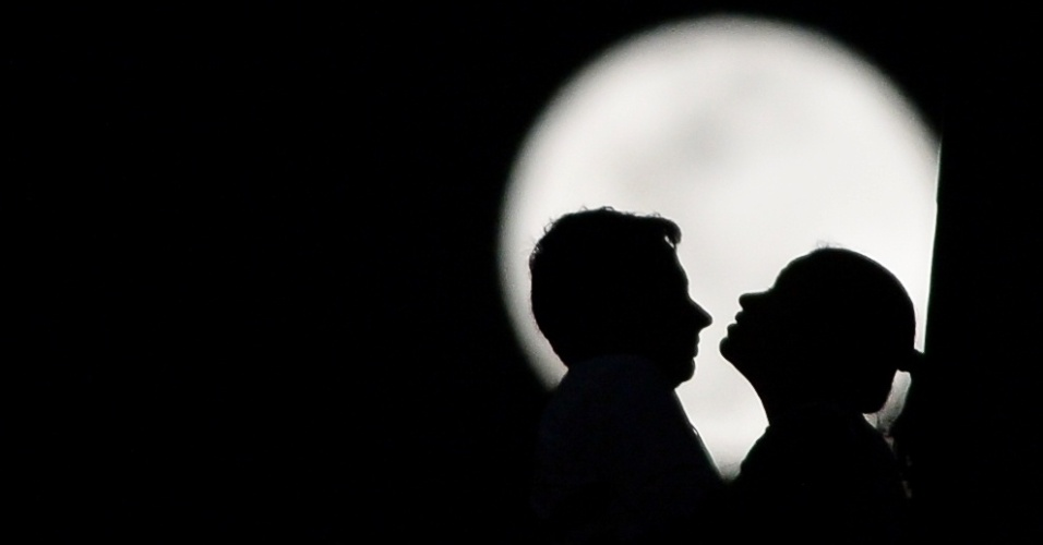 29.ago.2015 - Casal se beija em São Paulo, neste sábado, com o a Superlua ao fundo. O evento acontece quando ocorre uma lua cheia no período entre 24 horas antes ou depois de a lua atingir o perigeu (ponto mais próximo da Terra) de sua órbita