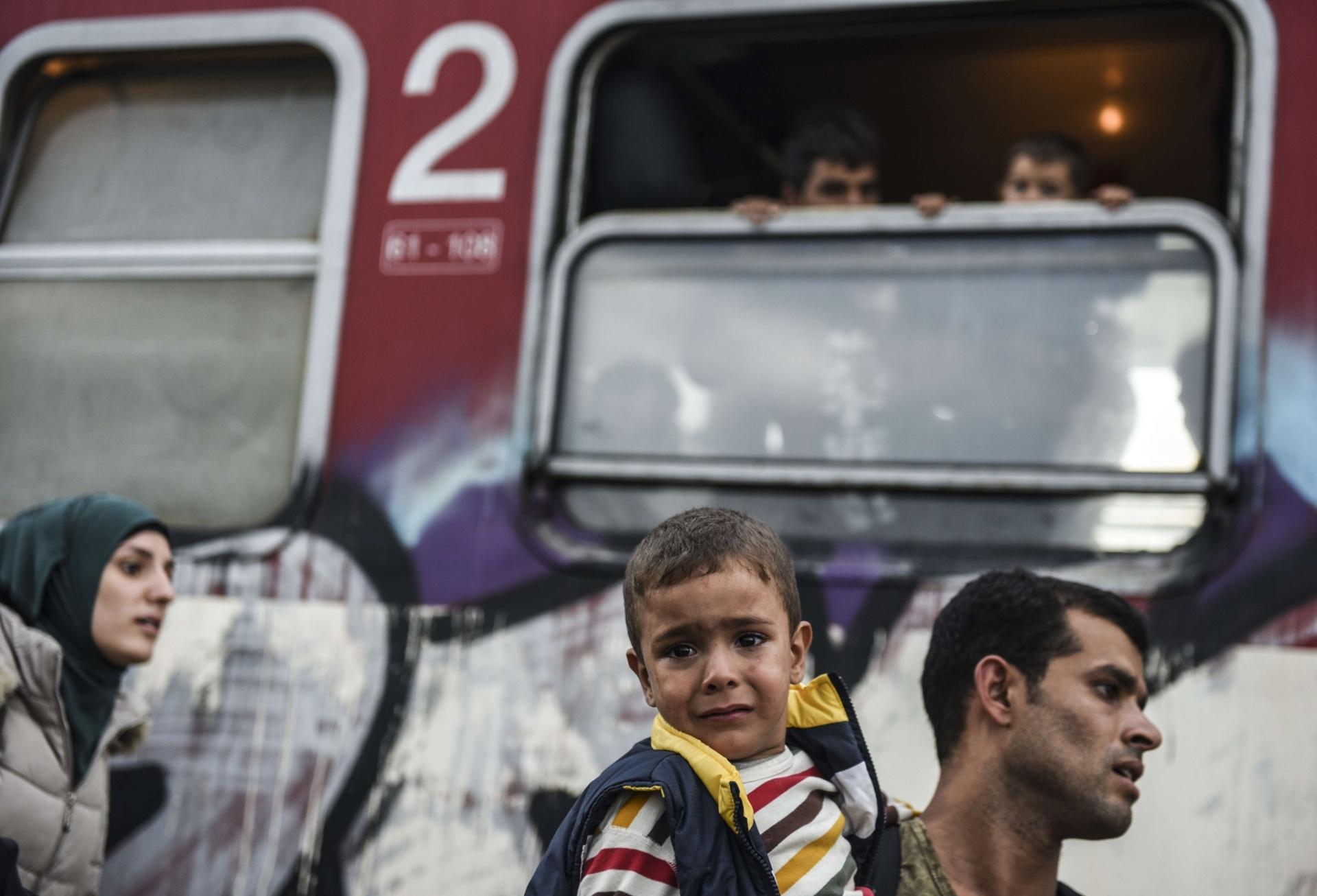 25.set.2015 - Refugiado carrega criança nos braços observados por pessoas a bordo de um trem de passageiros para imigrantes e refugiados partindo da Macedônia em direção à Sérvia, nesta sexta-feira (25). Os líderes da União Europeia realizaram na última quarta uma reunião de emergência para discutir a crise de imigração no continente, levando a um acordo para realocar 120.000 refugiados entre os países membros da UE (União Europeia)