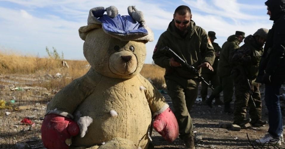 13.out.2015 - Rebeldes pró-Rússia passam armados ao lado de urso de pelúcia enquanto procuram por artefatos explosivos nas proximidades do aeroporto internacional de Donetsk, na Ucrânia. As forças ucranianas perderam o controle do aeroporto desde janeiro deste ano