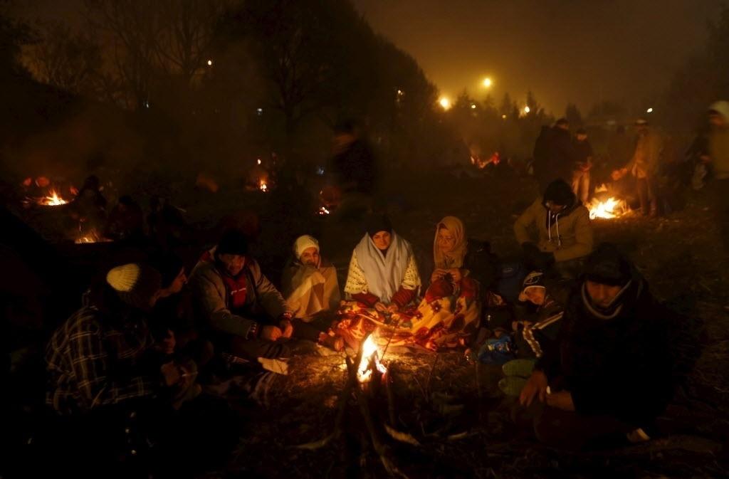 27.out.2015 - Imigrantes usam fogueira para se aquecer enquanto aguardam na fronteira entre Eslovênia e Áustria. A temperatura na região fica entre 8ºC e 6ºC. A Eslovênia pretende convocar empresas privadas de segurança para ajudar a gerenciar o fluxo de milhares de imigrantes que atravessam o país em direção ao norte da Europa