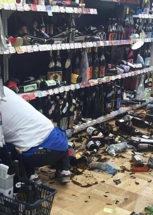 Funcionária limpa garrafas que quebraram após tremor na cidade de Kumamoto, no Japão