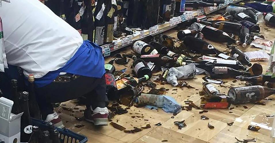 14.abr.2016 - Funcionária limpa garrafas que quebraram após tremor na cidade de Kumamoto, no Japão