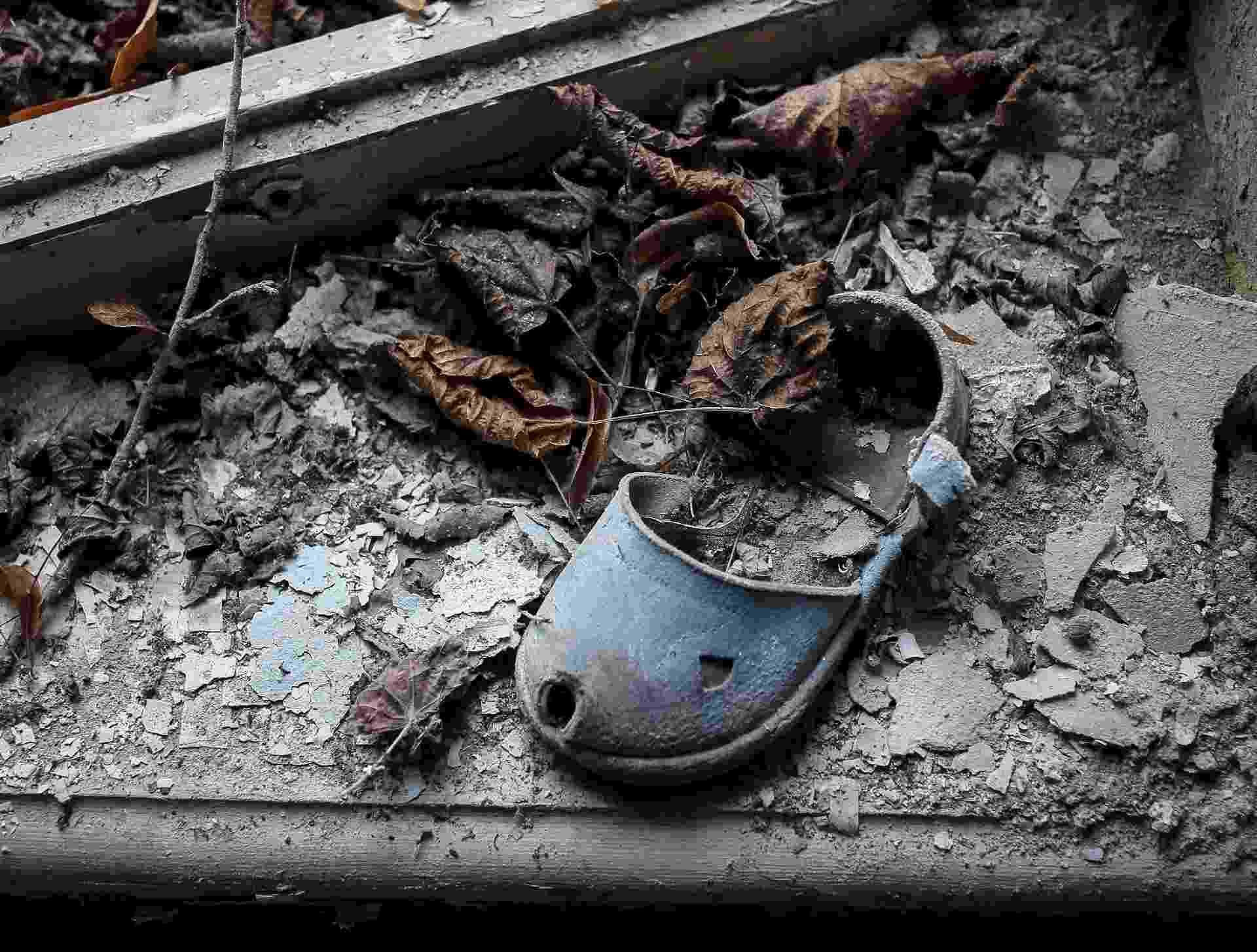 Em 2016, o acidente nuclear de Tchernóbil, na Ucrânia, completa 30 anos. A catástrofe de 1986 aconteceu após, entre outros erros, os funcionários terem fechado o sistema hidráulico que controlava as temperaturas do reator. Após entrar em processo de superaquecimento, uma imensa bola de fogo anunciava a explosão do reator rico em Urânio-235, elemento químico de grande poder radioativo. Na foto, um chinelo de criança deixado num jardim de infância na cidade de Pripyat, próxima à usina - Gleb Garanich/Reuters