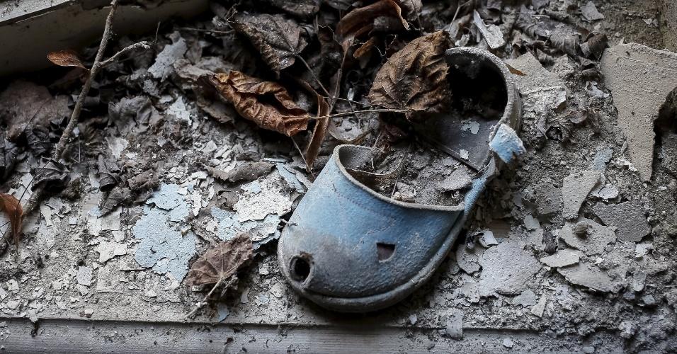 Em 2016, o acidente nuclear de Tchernóbil, na Ucrânia, completa 30 anos. A catástrofe de 1986 aconteceu após, entre outros erros, os funcionários terem fechado o sistema hidráulico que controlava as temperaturas do reator. Após entrar em processo de superaquecimento, uma imensa bola de fogo anunciava a explosão do reator rico em Urânio-235, elemento químico de grande poder radioativo. Na foto, um chinelo de criança deixado num jardim de infância na cidade de Pripyat, próxima à usina