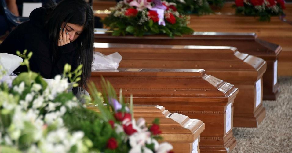30.ago.2016 -  Mulher presta respeito a vítima durante funeral em Amatrice, Itália