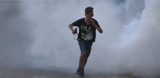 Garoto palestino corre durante confronto entre manifestantes e forças de segurança israelenses nas proximidades de Jerusalém