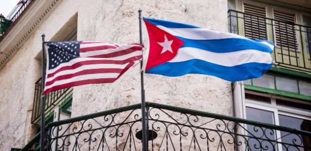Bandeiras dos EUA e de Cuba lado a lado em sacada de apartamento em Havana