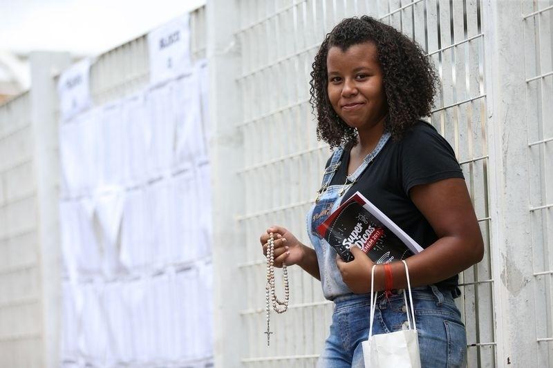 12.nov.2017 - Com terço na mão, candidata aguarda abertura dos portões em Brasília para o segundo dia de prova do Enem