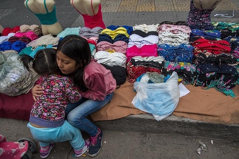28.nov.2017 - Gabriela, 1, e sua prima Leila, 7, brincam no ponto de venda da família. De origem peruana, seus pais costuram as roupas que, depois, eles mesmos vendem na feirinha