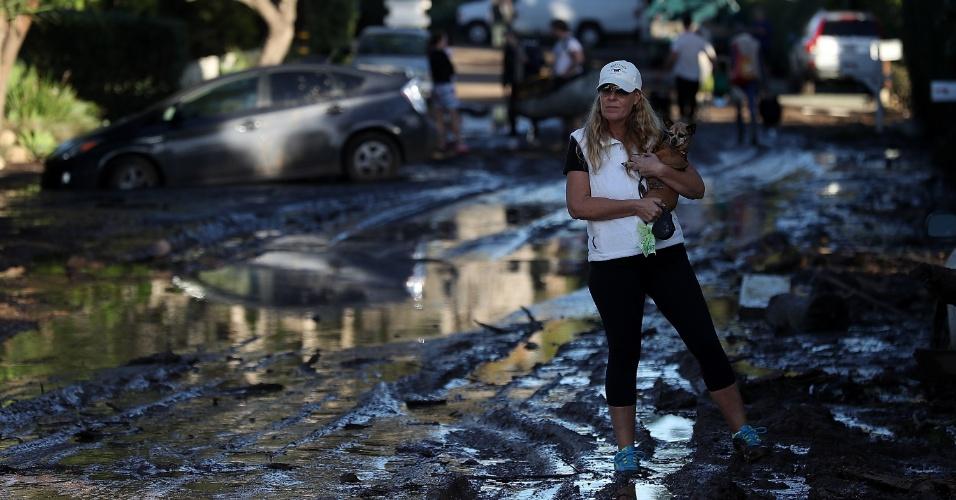 10.jan.2018 - Moradora de Montecito carrega seu cachorro em rua afetada pelos deslizamentos ocorridos na terça-feira
