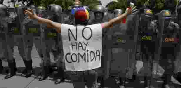 """Mulher usa blusa onde se lê """"não tem comida"""" durante protesto em Caracas - Federico Parra/ AFP"""